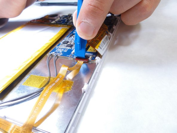 Using a plastic opening tool, lift open the tab that holds the connection between the camera and motherboard in place. The ribbon cable will become detached.