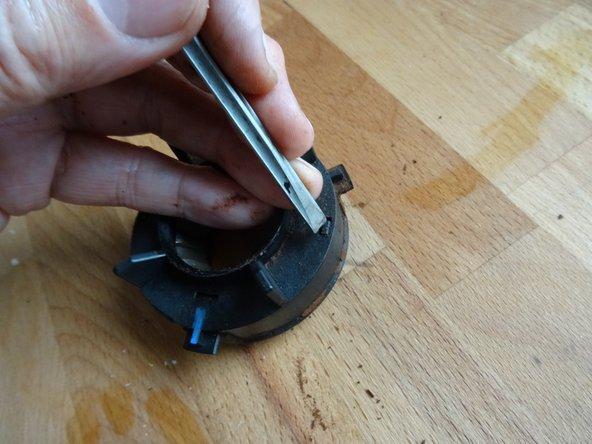 Die Kappe des Mahlrings kann entfernt werden, indem man die kleinen Rasten abwechselnd links und rechts mit einen Schraubenzieher eindrückt.