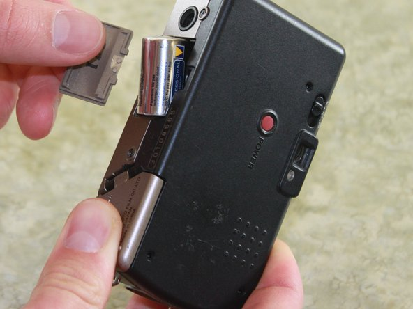 Remove the battery from the camera by pulling the battery door outwards.