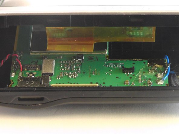 This releases the ribbon cable separating the two halves of the device.