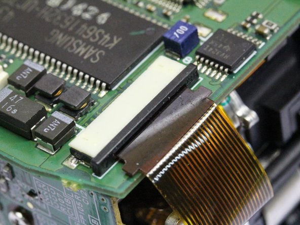 Disconnect the bottom left ribbon cable. Hook your fingernails behind the right and left notches of the black connector part, and pull it towards the brown ribbon cable with even and L/R balanced force until loose. FRAGILE ! The cable will slide out easily.
