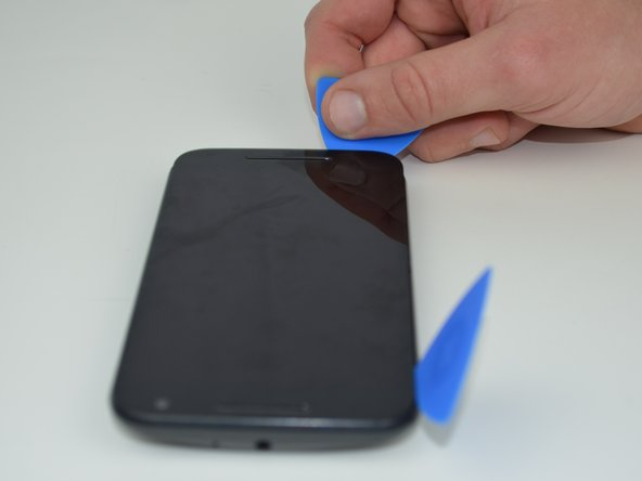 Use an opening pick to hold that edge in place and continue this process around the entire screen, applying more heat as necessary.