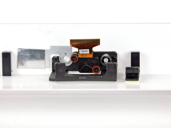 Image 1/2: Remove the small black plastic camera bracket from the front bezel.