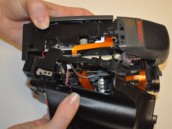 Image 3/3: Begin separating the plastic casing from the inner components of the device.