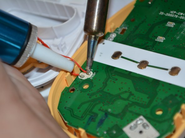 Image 2/2: Flip over the motherboard and  de-solder the wires connecting the speaker to the motherboard