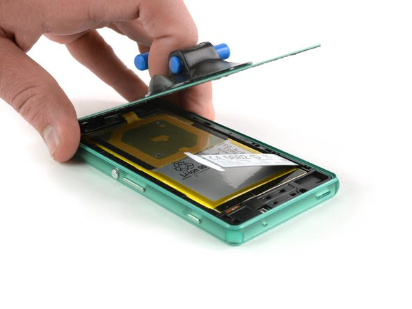 Move the pick carefully around the edges to loosen the adhesive on every side of the phone.