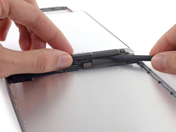 Push gently between each of the two adhesive tabs; be careful not to damage any of the nearby cables.