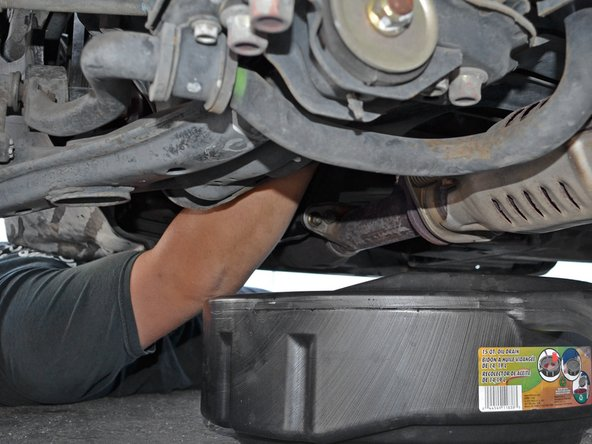 To reach the oil filter, guide your hand around the back side of the drive axle and up toward the top of the engine.