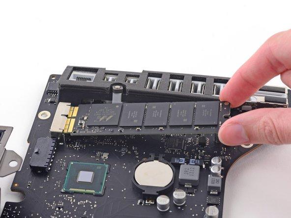 Hebe die SSD an der Kante ganz rechts etwas an und ziehe sie recht kräftig gerade aus ihrem Sockel auf dem Logic Board heraus.