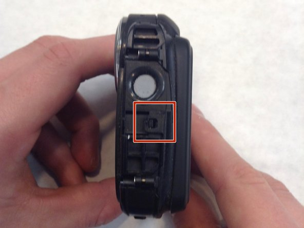 Unlatch the four clasps located on each side of the camera by hand.