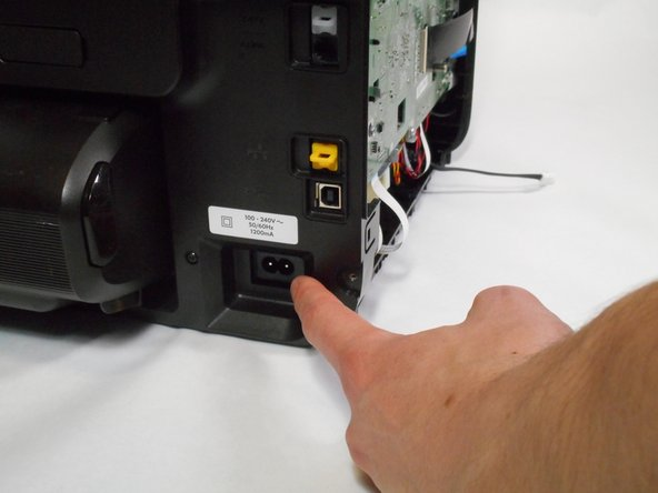 Place your left hand on the left side of the power supply through the opening in the side of the printer.