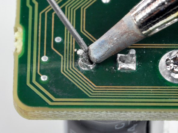 Image 1/3: Place the tip of the soldering iron against the solder pad.