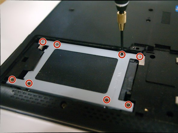 Image 1/2: The hard drive cover can now be removed by lifting the tab on the left.