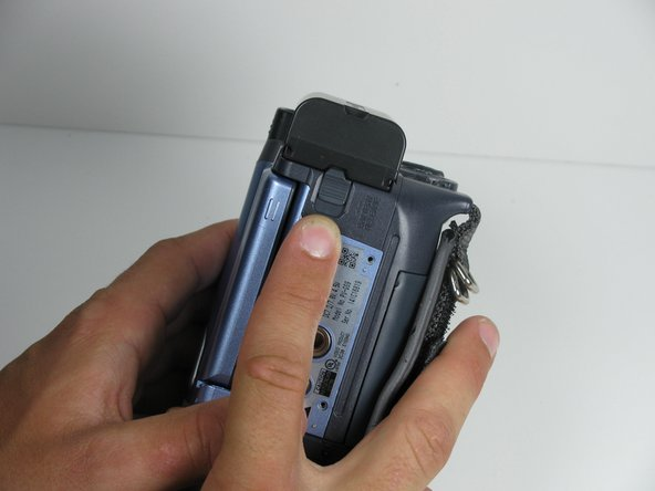 While holding the Camcorder firmly, pull down on the battery removal tab located on the underside of the camcorder.