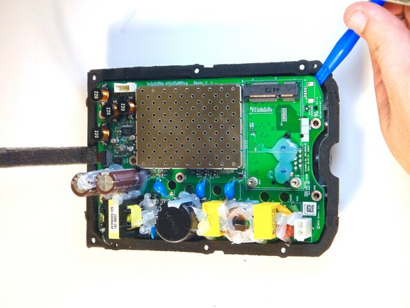 Using a plastic opening tool, remove the motherboard  from the rear housing cover.