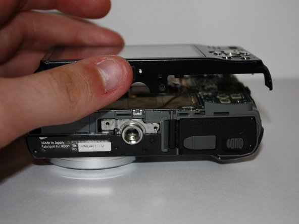 Carefully separate the back of the camera from the main body
