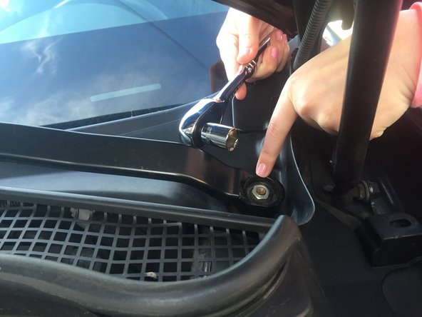 After removing the bolt cover, you will find the bolt that holds the wiper arm onto the vehicle.