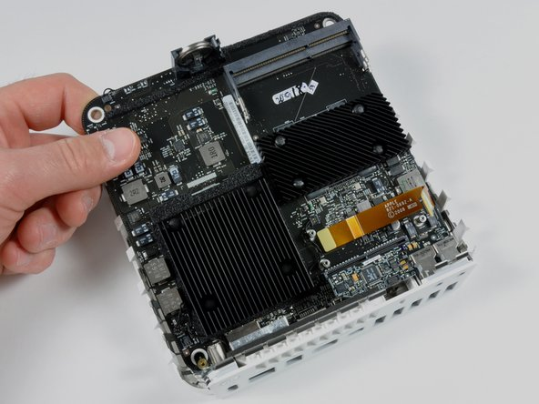 Grasp the logic board with your hand and pull it away from the I/O ports.