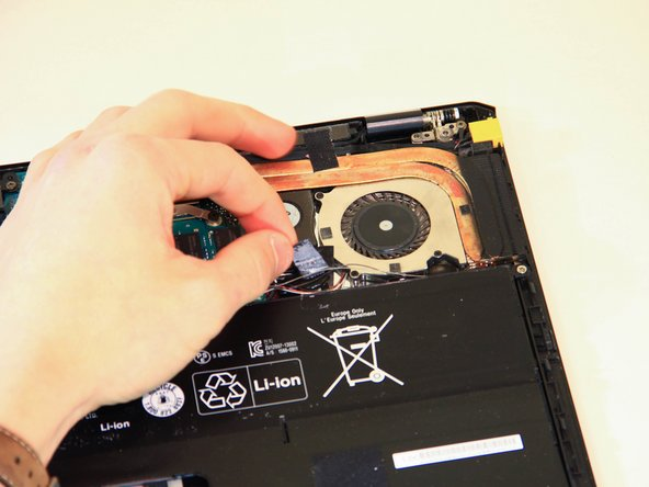 Once the bottom cover is removed, peel away the piece of tape located near the fan and heat sink assembly.