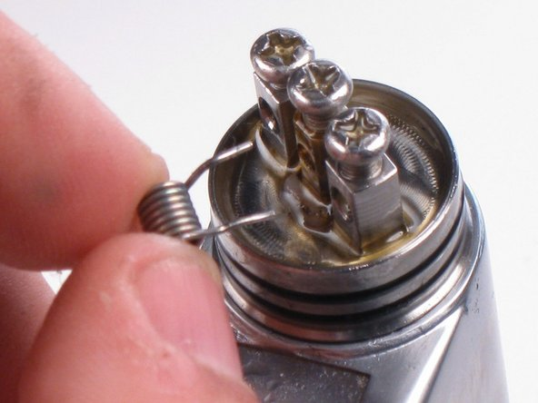 Place the new coil into the holes underneath the positive and negative screws.