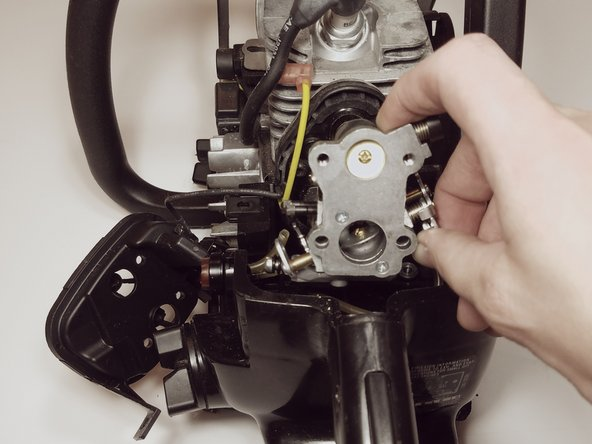 Slide the carburetor assembly off the mounting bolts and away from the engine
