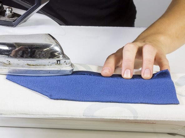 Fold over the seam allowance on the patch and iron it down – this will help with sewing the patch on.