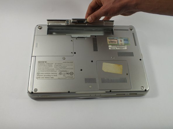 Image 2/2: While holding the release switch to the left,  lift the battery.