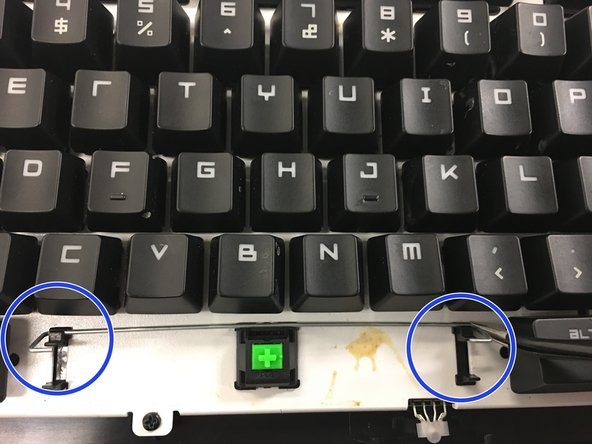 Using tweezers unfasten the metal bar from the keyboard itself both places that they are connected.