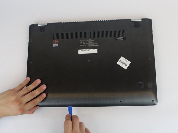 Using a plastic opening tool, pull out the back panel from the laptop.