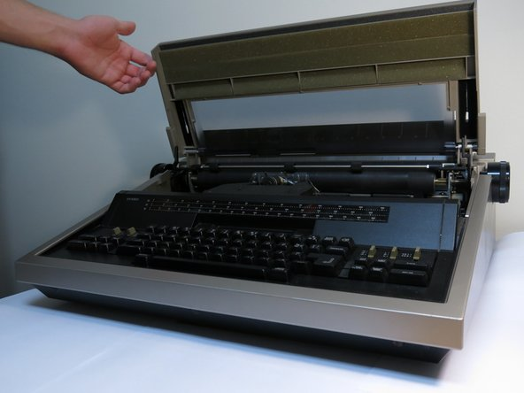 Open the lid of the typewriter.