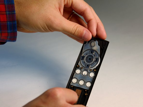 Locate the black plastic tab at the top end of the button panel, grab it with your fingers and pull back to separate the button panel from the remote control's case.