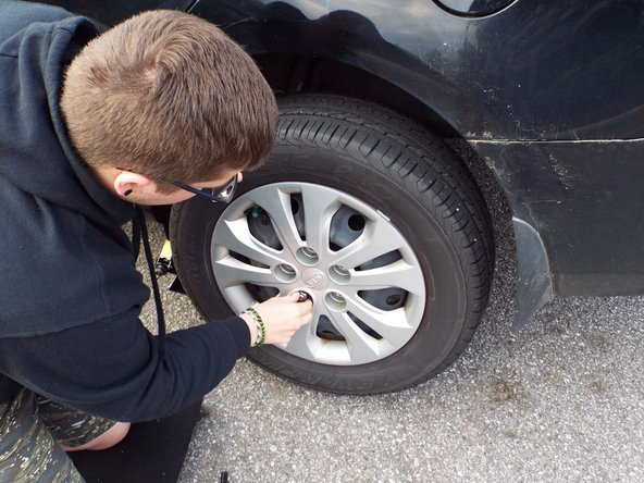Once tire is elevated, remove lug nuts by hand.
