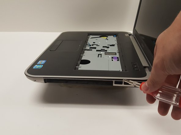 Separate the palm rest from the bottom base using the 2.0mm flat head screwdriver as a lever.