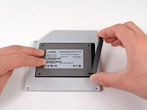 Image 1/2: Once the hard drive is snug, reinsert the plastic positioner while holding the hard drive against the bottom of the enclosure.