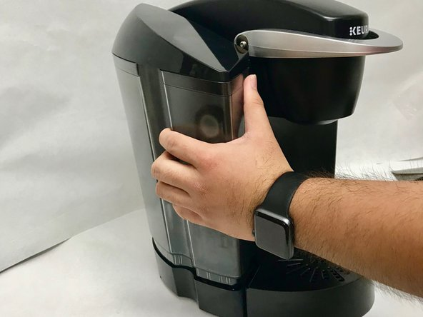 Remove the water reservoir from the Keurig machine by gently lifting up on the reservoir and pulling it away.