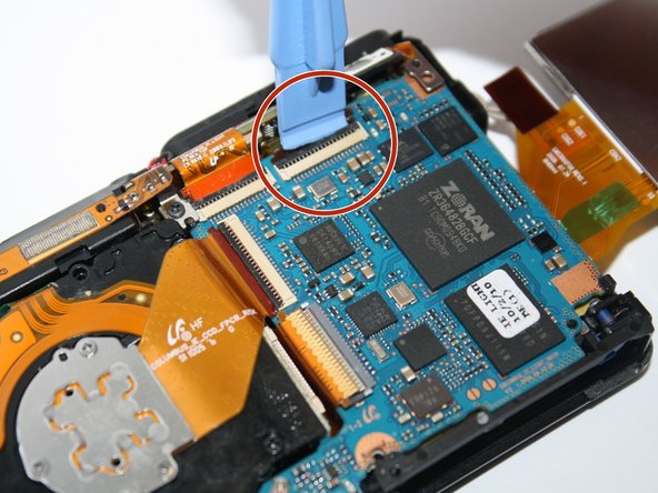Unclip the four connecters that hold down the orange copper film strips with the plastic opening tool.