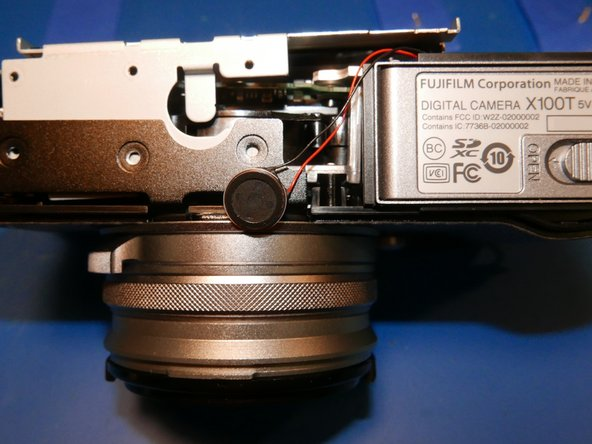 The speaker is held into place by double sided tape. Pull it off the steel frame and move it toward the bottom of the camera