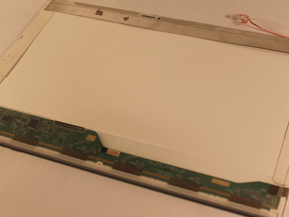With the screen now removed from the computer, remove the two screws from the screen's metal enclosure.