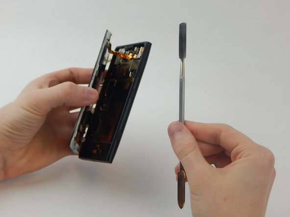 Wedge a spudger underneath the silver rectangle in the upper right corner until it pops off the back of the phone.