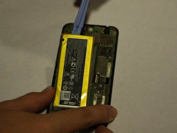 Using the plastic opening tools, lift the battery up from its slot