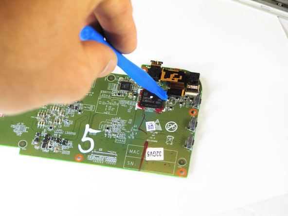 Use small plastic opening tool to pry rear facing camera flat top connector from motherboard.