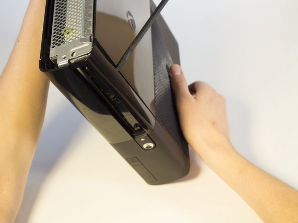 Image 1/3: Rotate the Xbox to the left to locate the clip connecting the front panel to the body. Insert the spudger inside the gap to release the clip. This may require wiggling the spudger. The clip will pop off, making the front panel looser.