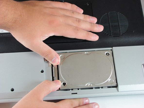 Image 1/3: Lift the hard drive out of the hard drive bay, left side first.