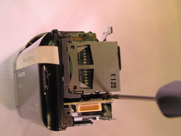 Remove the black 4 mm screw located on the back of the camcorder under the SD card slot.