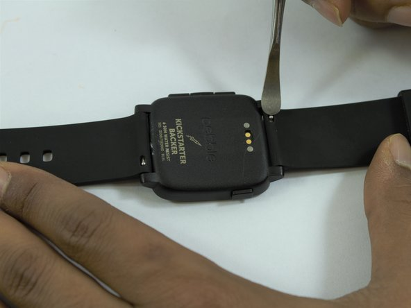 Image 1/2: Hold the watch securely and press the spring latch component towards you with the metal spudger tool.