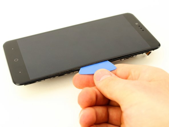 Insert a plastic opening tool between the screen and the rear case and separate it carefully, starting at the bottom.