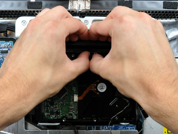 Image 2/2: Press the hard drive bracket down toward the bottom edge of your iMac to free it from the rear case, then rotate the top of the drive toward yourself.