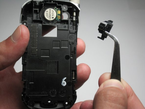 Using tweezers or your hands, pick out the semicircular plastic border between the speaker and headphone jack