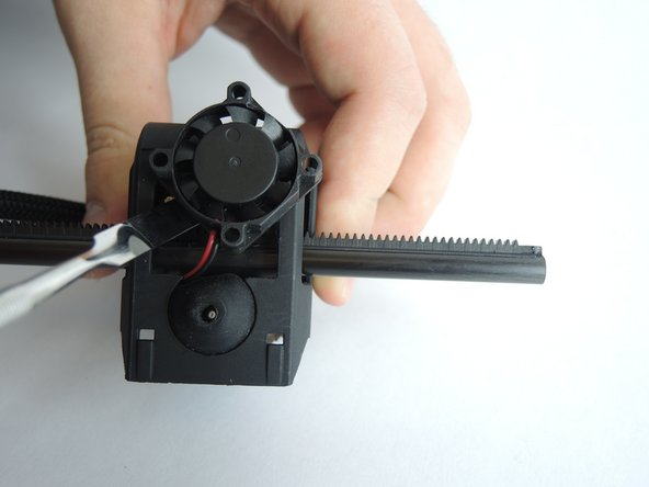 The fan is held loosely in place at the base of the printer head. Use a metal spudger to gently pry it out of the printer head.