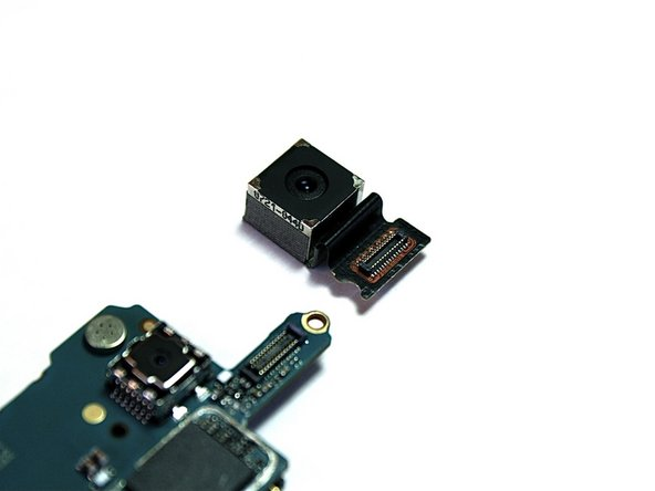 Image 3/3: Then, hold and remove the rear camera using your thumb and index finger. It should detach along with the connector. Finally, set the rear camera aside.